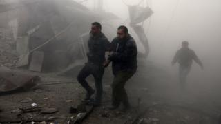 A wounded man is helped from the scene of a reported government air strikes on the town of Arbin, in the besieged rebel-held Eastern Ghouta (8 February 2018)