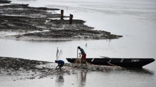 Nigerian fisherman work on a river blackened by oil pollution