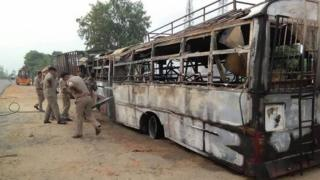 Police officers inspecting the charred bus after the collision