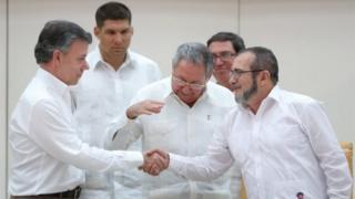 President Raul Castro (centre) reacts as Colombia's President Juan Manuel Santos (left) and Farc rebel leader Rodrigo Londono, better known by the nom de guerre Timochenko, shake hands in Havana on 23 September, 2015
