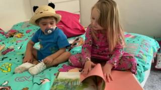 Stanley Dalton with his sister Delilah, as she reads him a book