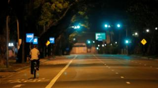 A man rides his bicycle along a road during the curfew after multiple explosions