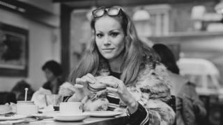 Claudine Auger eating a burger in London in 1968