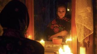 Uma garota em frente ao espelho com uma vela na mão