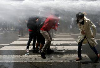 Nepalese youths are sprayed with a water cannon