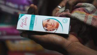 Woman holding a 'Fair & Lovely' brand product