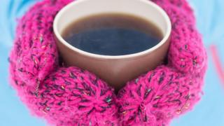 A person wearing mittens clasping a hot drink