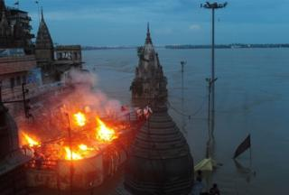 Indian mourners perform a cremation on the roof of a building overlooking The Manikarnika Ghat in Varanasi on August 23, 2016.
