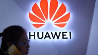 A woman uses a phone in front of Huawei logo