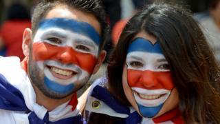 Dos costarricenses con los rostros pintados
