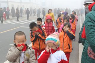Pupils cover their noses after school in heavy smog on 23 December 2015 in Binzhou, China.