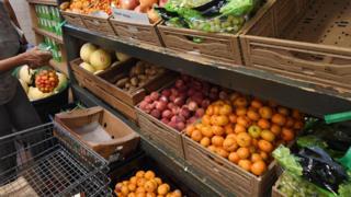 Woman at food bank choosing produce, Los Angeles (24 July 2019)