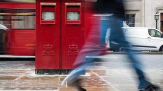 A pedestrian walks past a post box