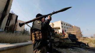 Membro das Forças de Operações Especiais do Iraque carrega um lançador de foguetes na Universidade de Mossul