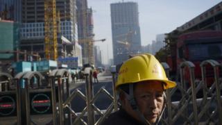 12月13日,北京,一處工地前的建築工人。
