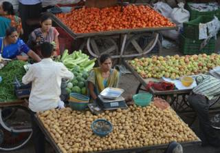 An Indian vegetable vendor (C) waits for customer at a market in Ahmedabad on October 22, 2013.