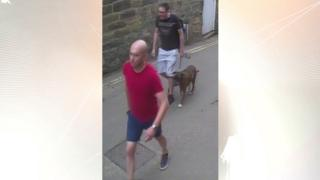 CCTV image of two men walking along a street, one holding a lead with a dog