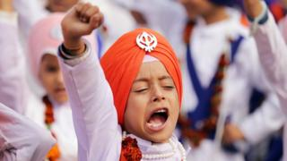 A young Sikh wearing an orange turban joins in celebrations