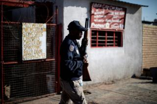 A South African police officer holds a rifle as he stands in Soweto