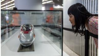 A girl looks at a model of the 'Vibrant Express' train on display at the West Kowloon terminus during an open day to the public in Hong Kong on September 1, 2018.