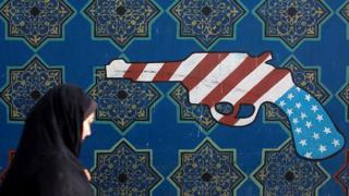 Женщина проходит мимо граффити в Тегеране