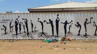 Painted silhouetted figures take axes to their legs, which are drawn with roots of a tree, instead of feed