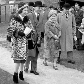 Queen Elizabeth II (left) wearing a leopard-skin coat at a Sandown Park race meeting.