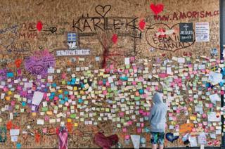 A young boy looks at notes on a wall.