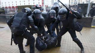 riot police arrest a man