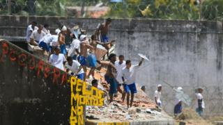 Inmates remain atop the prison roof during a riot at Alcacuz PPrison, near Natal in Rio Grande do Norte, Brazil on 19 January