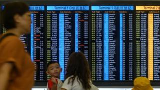 Passengers check the status of their flights on an electronic board at Hong Kong international airport on August 14, 2019.
