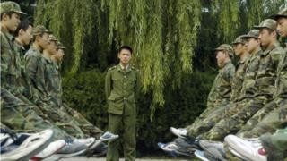 Un grupo de jóvenes formados frente a un instructor uniformado