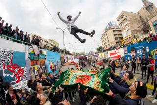 A young Iraqi protester is blanket-tossed into the air by fellow demonstrators as anti-government rallies continue in Tahrir Square in the capital Baghdad.