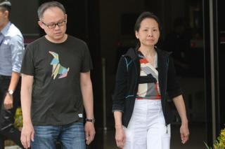 Trader Lim Choon Hong (L) and his wife, Chong Sui Foon (R), both 47, leave the state court in Singapore on March 23, 2016.