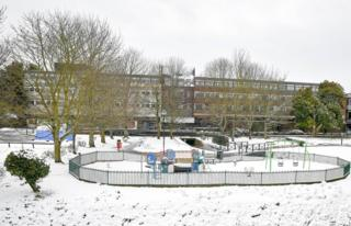 A snow covered playground next to a building block.