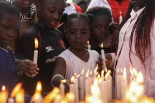 Children light candles during an event to pray and remember those who have lost their lives due to HIV/Aids, during World AIDS Day in Kariobangi, Nairobi, Kenya on 1 December 2019