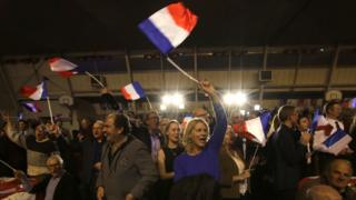 Supporters of far right National Front party regional leader for southeastern France, Marion Marechal-Le Pen, wave flags at a meeting after the results of the first round of the regional elections, in Carpentras