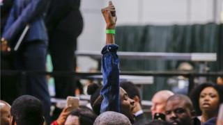 """A protester chanting """"Black Lives Matter"""" is escorted by security personnel after interrupting Democratic 2016 US presidential candidate Hillary Clinton"""