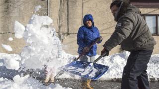 A family shovels snow