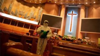 Trabalhador desinfetando uma igreja
