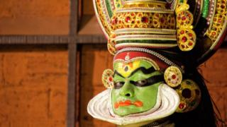Un actor con la cara pintada con maquillaje verde y sombras negras alrededor de los ojos y en la frente. También tiene un elaborado sombrero ornamental.