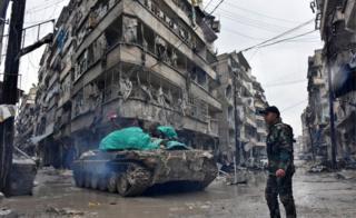 アレッポのジスル・アル・ハジ交差点を通るシリア政府支持勢力(14日)