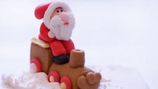 A sugar figurine of Father Christmas sitting on a train on a Christmas cake