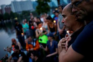Wilfredo Perez (L), a local bartender at a gay bar, is embraced by his partner Jackson Hollman during a vigil to commemorate victims of a mass shooting at the Pulse gay night club in Orlando, Florida, 12 June 2016