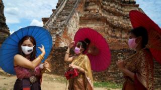 Women wearing protective face masks and dressed in traditional costumes visit Wat Chaiwatthanaram in Thailand.