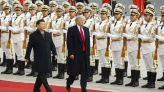 Trump e Xi caminham em tapete vermelho e em frente a guardas em encontro que teve lugar em Pequim no ano de 2017