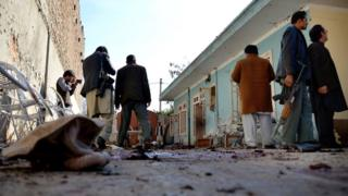 Afghan security forces inspect the site of the suicide attack.