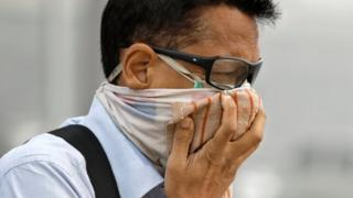 Un hombre se cubre la boca por las calles de Nueva Delhi.