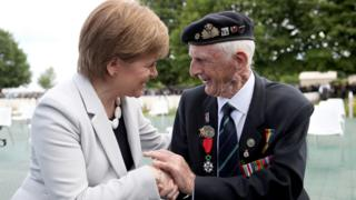 First Minister Nicola Sturgeon sits with D-Day veteran John Greig, 95, from Dumfries, at the Commonwealth War Graves Commission Cemetery in Bayeux