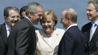 Italian Prime minister Romano Prodi, French President Nicolas Sarkozy (hidden), US President George W. Bush, German Chancellor Angela Merkel, Russian President Vladimir Putin and British Prime Minister Tony Blair share a laugh as they take position for a family picture with other G8 leaders,